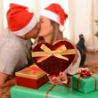 Young Happy Couple Kissing on rug at Christmas — Stock fotografie