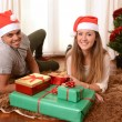 Young Happy Couple on rug at Christmas with Presents — Stock fotografie