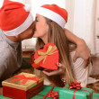 Young Happy Couple Kissing on rug at Christmas — Stock Photo #35082723