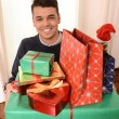 Young handsome man holding Christmas Presents — Stock Photo