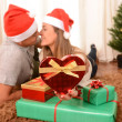 Young Happy Couple Kissing on rug at Christmas — Stock Photo