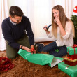 Young Happy Couple wrapping Christmas presents — Stock Photo #35083109