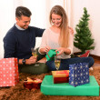 Young Happy Couple opening Xmas presents — Stock Photo #35083459