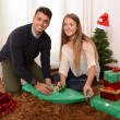 Young Happy Couple wrapping Christmas presents — Stock Photo