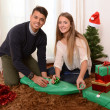 Young Happy Couple wrapping Christmas presents — Stock Photo #35084031