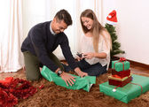 Young Happy Couple wrapping Christmas presents — Stockfoto