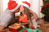 Young Happy Couple Kissing on rug at Christmas — Stockfoto