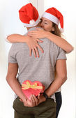 Young Couple kissing and hidden Christmas Present — Stockfoto
