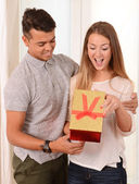 Young Beautiful Woman opening Present of her Handsome man — ストック写真