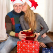 Stock Photo: Young Happy Couple Kissing on rug at Christmas