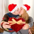 Romantic Young Happy Couple Christmas hats  kissing  — Stock Photo