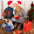 Young Happy Couple Kissing on rug at Christmas — Стоковая фотография