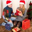 Young Happy Couple with Presents on rug at Christmas — Stock Photo