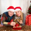 Young Happy Couple with Presents on rug at Christmas — Stock Photo #36136235
