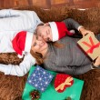 Young Happy Couple with Presents on rug at Christmas — Стоковая фотография