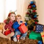 Little kids on rug opening Christmas Presents — Stock Photo #36138709