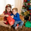 Little kids on rug opening Christmas Presents — Stock Photo