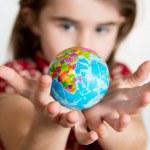 Cute lgirl holding little World Globe on her Hands — Stock Photo #36138875