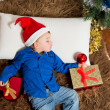 Cute Little boy in Santa Claus hat sleeping on Rug — Stock Photo