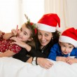 Happy Mum, daughter and little son playing at Christmas — Stock Photo