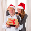 Stock Photo: Young Happy Couple with Presents on rug at Christmas