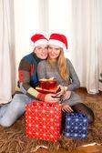 クリスマスで敷物の上で若い幸せなカップルを提示します。 — ストック写真