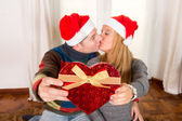 Romantic Young Happy Couple Christmas hats kissing — Stok fotoğraf