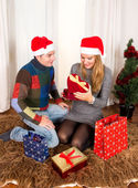 Young Happy Couple with Presents on rug at Christmas — Φωτογραφία Αρχείου
