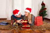 Young Happy Couple with Presents on rug at Christmas — Stockfoto