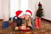 Young Happy Couple with Presents on rug at Christmas — 图库照片