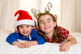 Happy cute little kid and his sister at christmas — Zdjęcie stockowe