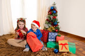 Little kids on rug opening Christmas Presents — Foto de Stock