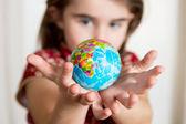 Cute lgirl holding little World Globe on her Hands — Stock Photo
