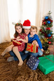 Young Mother in Santa Claus hat with son and daughter — Stock Photo