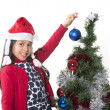 Little Happy Girl in Santa hat hanging Xmas Bubble — Стоковая фотография