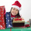 Cute Little Girl in Santa Claus hat holding Christmas Presents — Stok fotoğraf