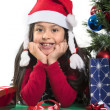 Cute Little Girl leaning on Presents smiling next to Xmas Tree — Stok fotoğraf