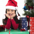 Cute Little Girl leaning on Presents smiling next to Xmas Tree — Stock Photo