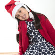 Cute Little Girl in Santa Claus hat sitting and Smiling at Xmas — Stock Photo