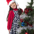 Cute Little Girl in Santa Claus smiling next to Xmas tree — Stock Photo