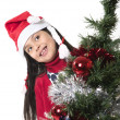 Cute Little Girl in Santa Claus smiling next to Xmas tree — Stock Photo #36450487