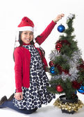 Little Happy Girl in Santa hat hanging Xmas Bubble — Stock Photo