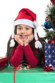 Cute Little Girl leaning on Presents smiling next to Xmas Tree — Foto de Stock