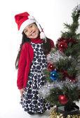 Cute Little Girl in Santa Claus smiling next to Xmas tree — Zdjęcie stockowe