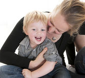 Young mother hugging her cute blond little child — Stockfoto
