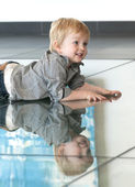 Little child playing with his reflexion on the floor — Stock Photo