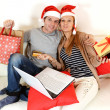 Young couple with laptop online shopping Christmas presents — Stockfoto