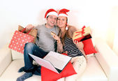 Young couple with laptop online shopping Christmas presents — Stock Photo