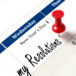 Pin on calendar pointing new year resolutions — Stock Photo