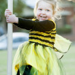 Little blond girl in bee costume playing outdoors — Stock Photo